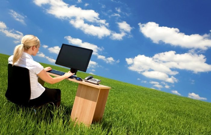 Business concept shot of a beautiful young woman sitting at a desk using a computer in a green field with a bright blue sky with fluffy white clouds. Shot on location.