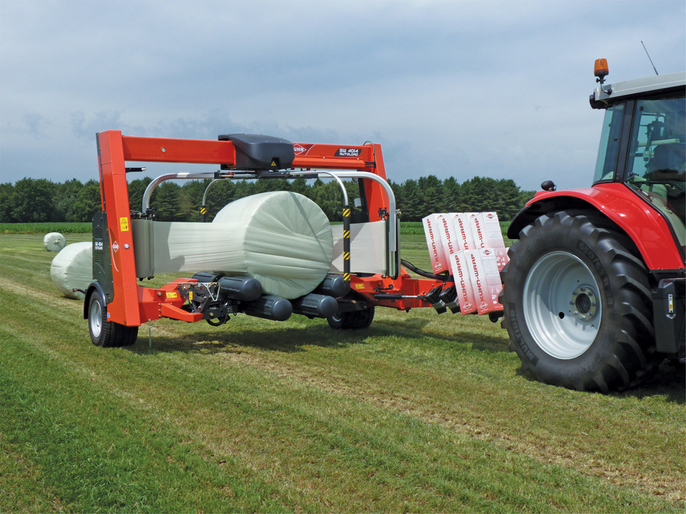 The SW 4014 bale wrapper from Kuhn uses an autoload feature which allows the tractor to continue moving while the bale is loaded, wrapped and set back down.