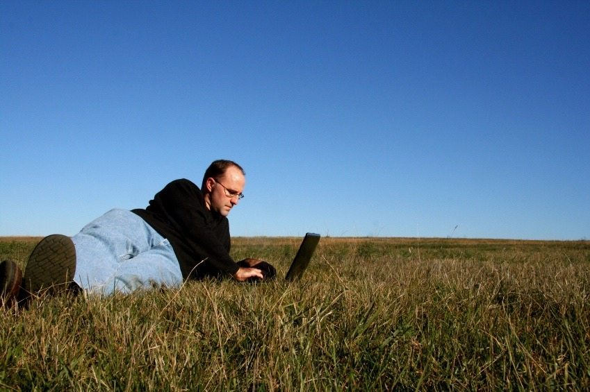 Man at work on laptop lying in grassy field.