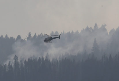 A helicopter flies over a wildfire south west of the town of Cache Creek, British Columbia, Canada July 18, 2017. Residents of the town were forced to evacuate 11 days ago and can now return to their homes. REUTERS/Ben Nelms - RC12041183D0